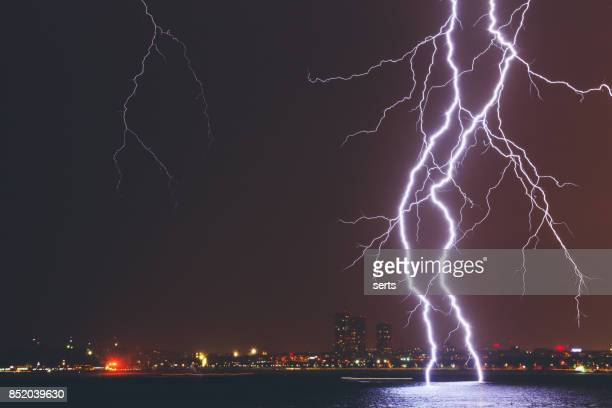 lightning strike over city - bolt stock photos and pictures