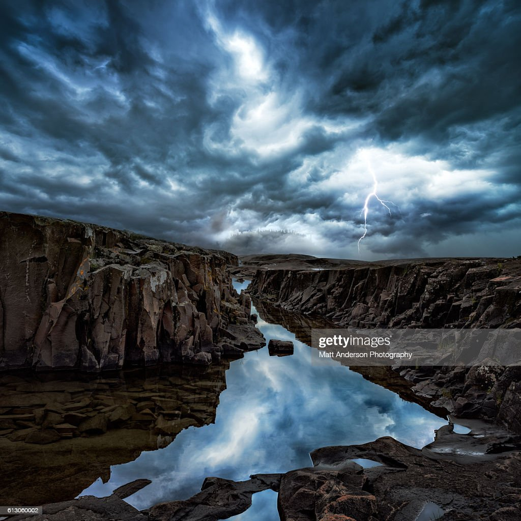 Thunderstorm with lightning strikes over a Lake Superior coastal shelf near Grand Marais, Minnesota. Crevices with pools of water reflect the storm clouds.