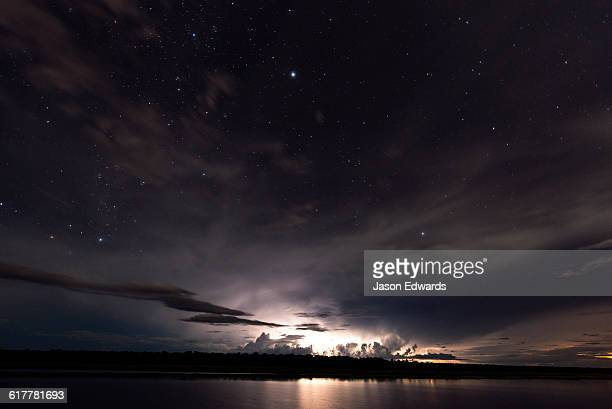 Lightning strikes a floodplain at night beneath a star-filled sky.