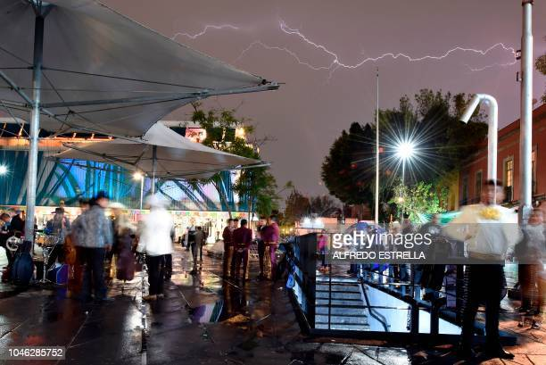 Lightning strikes above mariachi musicians gathered on Plaza Garibaldi in downtown Mexico City on October 5 2018 A serenade organized by mariachis...