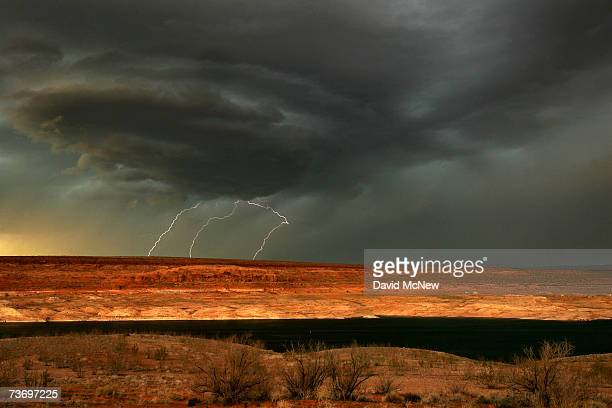 Lightning strikes as a muchneeded rain storm comes to Lake Powell which is marked by a 100foot thick bathtub ring of bleached sandstone the result of...