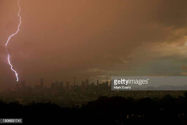 Lightning strikes as storm clouds move over the Sydney skyline on March 12, 2021 in Sydney, Australia. The Bureau Of Meteorology issued a warning...
