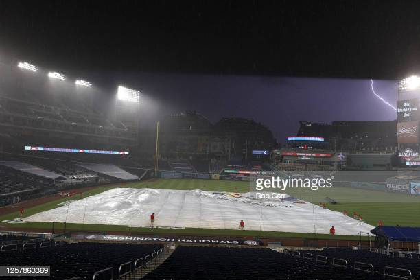 Lightning strikes as the Washington Nationals grounds crew covers the infield with a tarp as rain falls to delay the game against the New York...