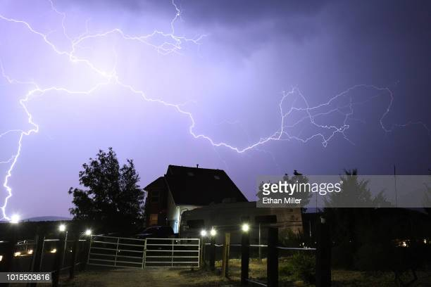 Lightning strikes behind a home in the community of Cold Creek as a line of monsoon storms sweep through the Mount Charleston Wilderness Area about...