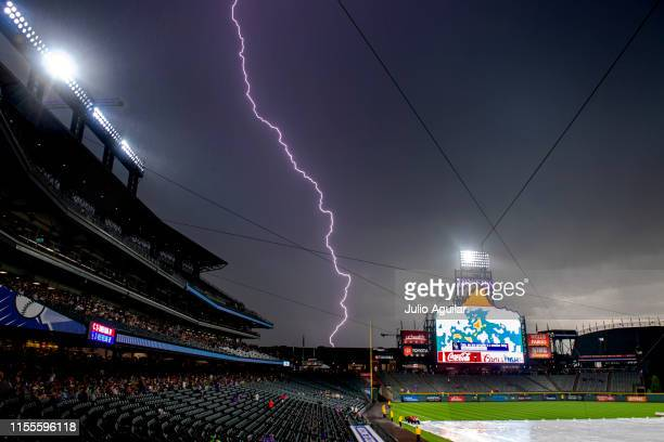 Lightning strikes behind Coors Field during a rain delay before a baseball game between the Cincinnati Reds and the Colorado Rockies on July 13, 2019...