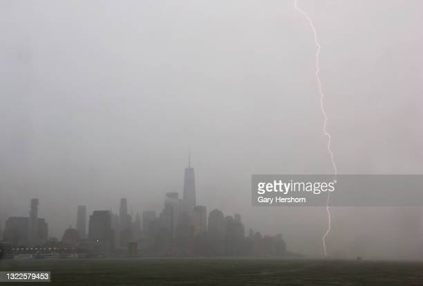 Lightning strikes in the Hudson River next to the skyline of lower Manhattan and One World Trade Center during a thunderstorm in New York City on...