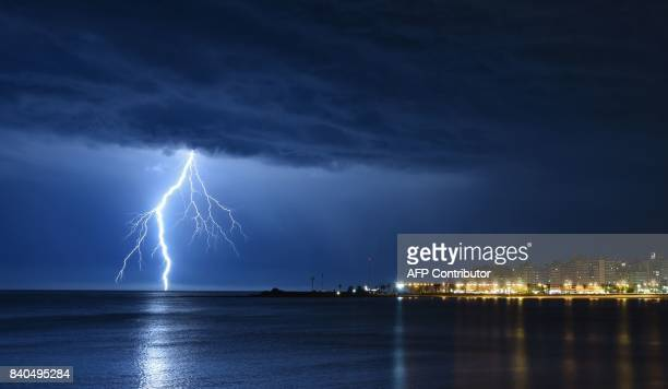 Lightning strikes off the coast of Montevideo late on August 28 2017 Following days of heavy rains flooding in Uruguay has forced almost 900 people...