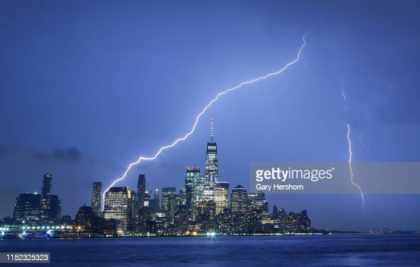 Lightning strikes on either side of One World Trade Center in lower Manhattan in New York City on May 28 2019 as seen from Hoboken New Jersey