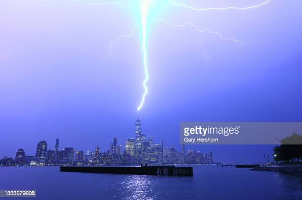 Lightning strikes One World Trade Center during a thunderstorm in New York City on August 11, 2021 as seen from Jersey City, New Jersey.