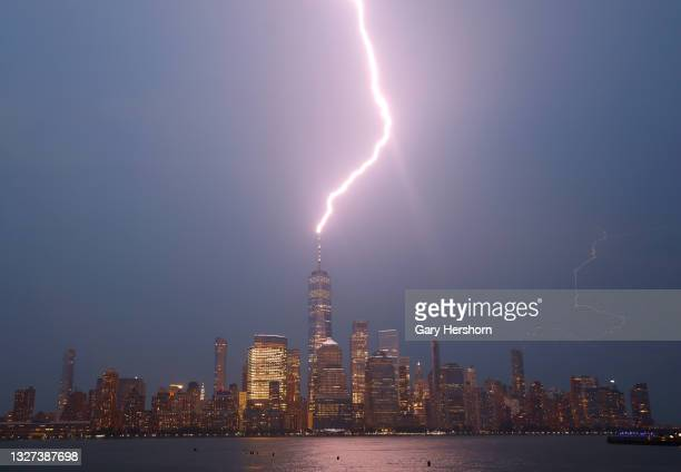 Lightning strikes One World Trade Center during a thunderstorm over lower Manhattan as the sun sets in New York City on July 6, 2021 as seen from...