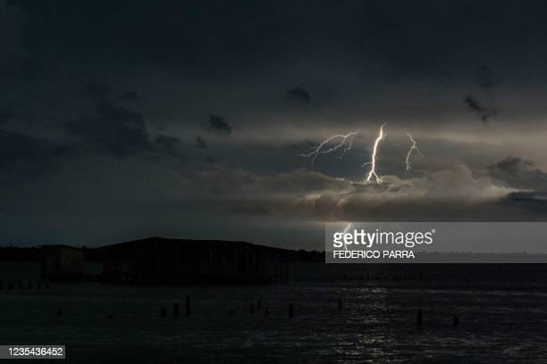 """Lightning strikes over lake Maracaibo near the stilt houses of Chamitas in Catatumbo, Venezuela, on September 11, 2021. - The """"Catatumbo Lightning"""",..."""