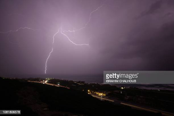 TOPSHOT Lightning strikes over the coastal city of Batroun to the north of the Lebanese capital Beirut on January 13 2019