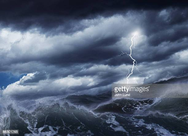 lightning striking over water - tempesta foto e immagini stock
