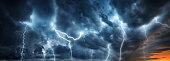Lightning thunderstorm flash over the night sky.