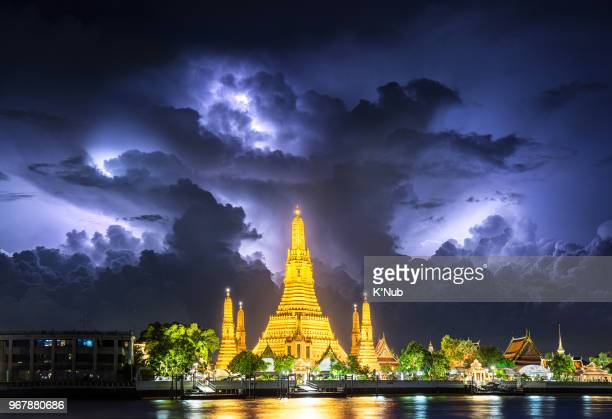 Lightning thunderstorm, rain, over Wat Arun, buddha temple famous landmark for travel by tourist on holiday in Bangkok city Thailand, Asia, after sunset time.