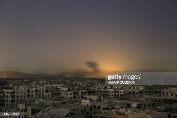 TOPSHOT Lights and smoke are seen during Syrian government bombardment on the rebelcontrolled town of Arbin in the besieged Eastern Ghouta region on...