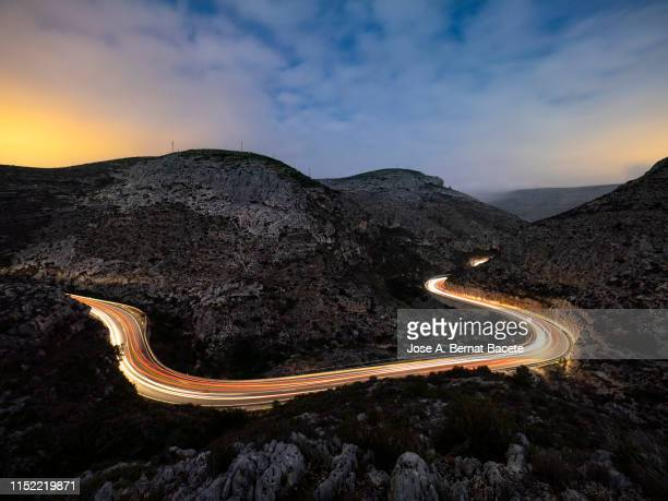 lights and trails of vehicles, cars and trucks, circulating along a road of mountain between ravines with circular curves closed in the night. - attività che richiedono movimento foto e immagini stock