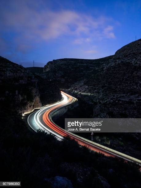 lights and trails of vehicles, cars and trucks, circulating along a road of mountain between ravines with circular curves closed in the night. valencia, spain - light trail stock photos and pictures