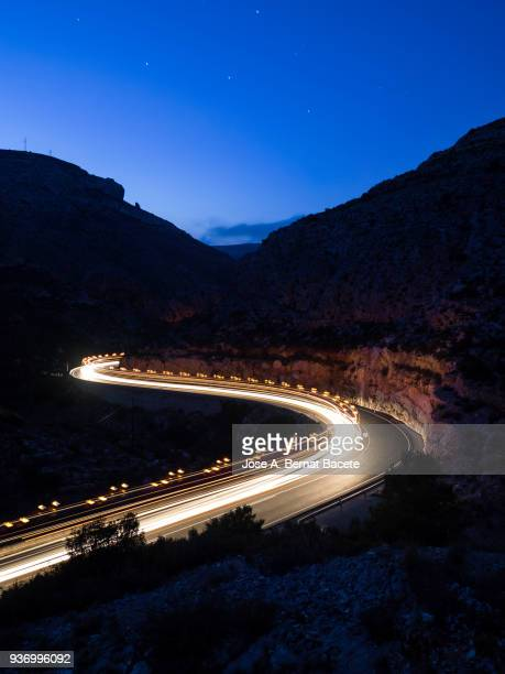 Lights and trails of vehicles, cars and trucks, circulating along a road of mountain between ravines with circular curves closed in the night.