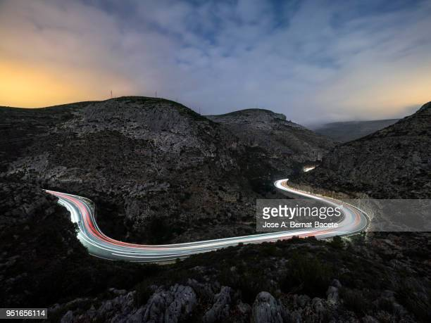 lights and trails of vehicles, cars and trucks, circulating along a road of mountain between ravines with circular curves closed in the night. - streak stock photos and pictures