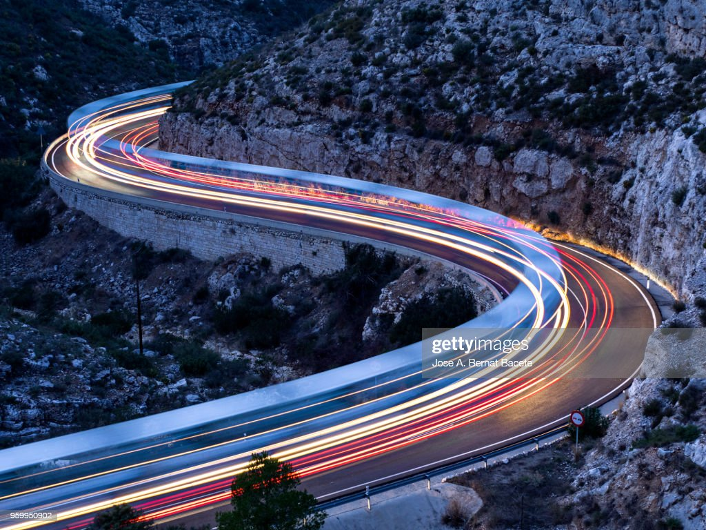 Lights and trails of vehicles, cars and trucks, circulating along a road of mountain between ravines with circular curves closed in the nightfall. : Stock-Foto