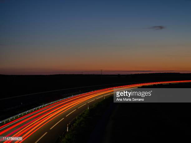 lights and trails of vehicles, cars and trucks, driving along a road with a curve at nightfall. - lineart stock-fotos und bilder