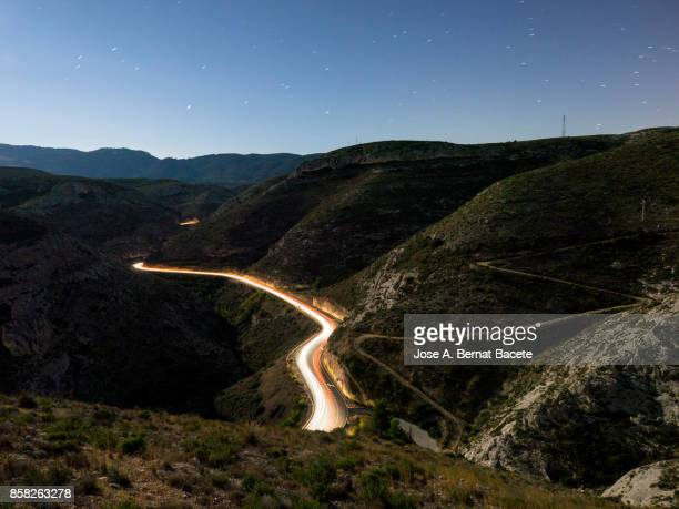 lights and trails of vehicles circulating along a road of mountain with curves closed in the night. valencian community, spain - vehicle light stock photos and pictures