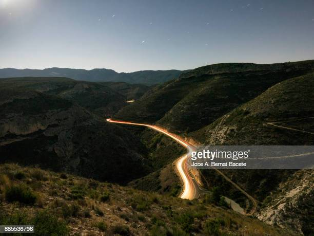 Lights and trails of vehicles circulating along a road of mountain with curves closed in the night. Valencian Community, Spain
