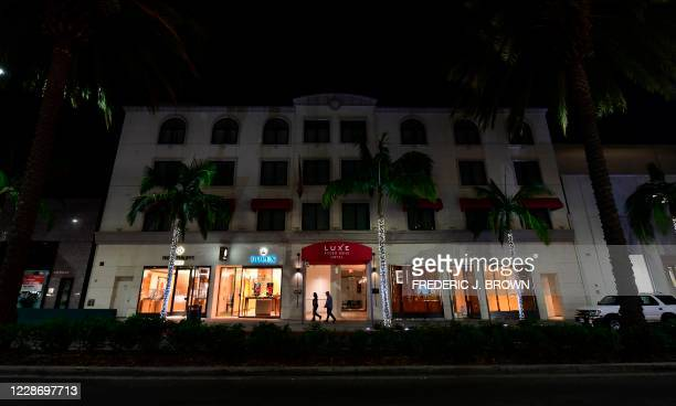 Lights are out at the Luxe Rodeo Drive Hotel as a couple walk past the entrance on September 24, 2020. - The hotel on the swanky Rodeo Drive has shut...