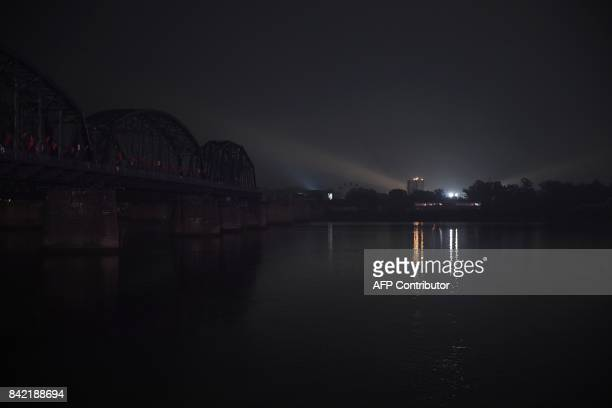 Lights are seen in the North Korean town of Sinuiju behind the Broken Bridge which once connected China and North Korea over the Yalu River at the...