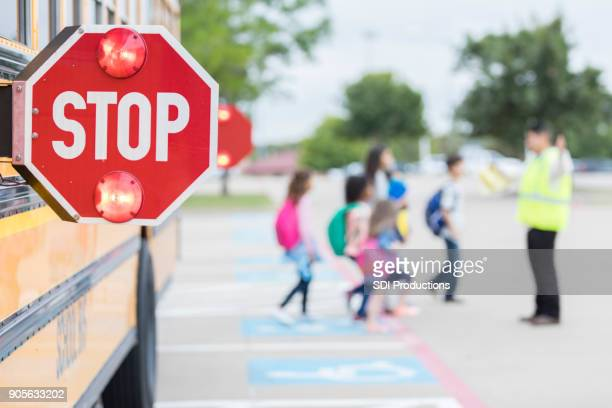 lights flash on a school bus stop sign as children cross street - psa stock photos and pictures