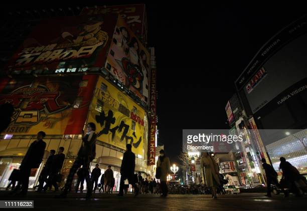 Lights for signs are turned off at buildings at night in Tokyo Japan on Monday March 28 2011 As Tokyo Electric Power Co the utility battling to avert...