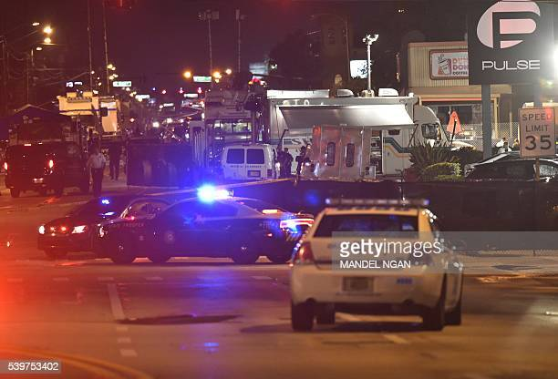 Lights from police vehicles light up the scene infront of the Pulse club in Orlando Florida on June 12 2016 Fifty people died when a gunman allegedly...