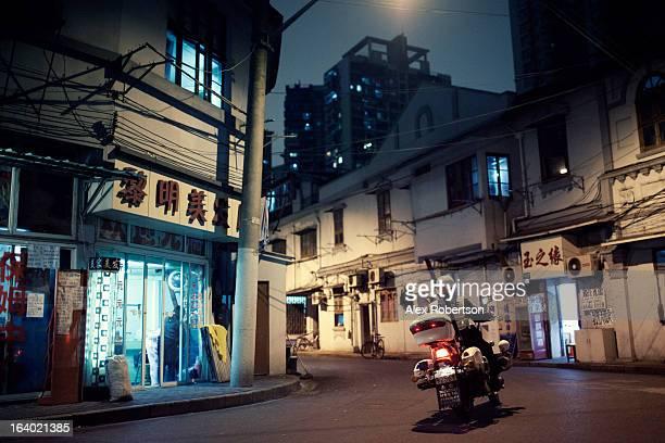 CONTENT] Lights glow at night on a deserted Shanghai street as a cop patrols on his motorbike