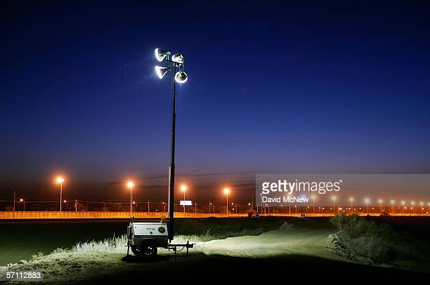 Lights illuminate a barren zone of graded earth and metal fences separating the US and Mexico on March 16 2006 near the border town of near San Luis...