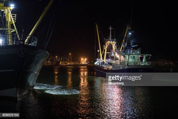 Lights illuminate a fishing trawler as it arrives with its catch before sunrise at the port of Den Helder Netherlands on Friday Aug 4 2017 Prime...