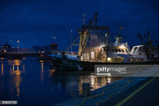 Lights illuminate a fishing trawler as it sits docked during unloading at the port of Den Helder Netherlands on Friday Aug 4 2017 Prime Minister...