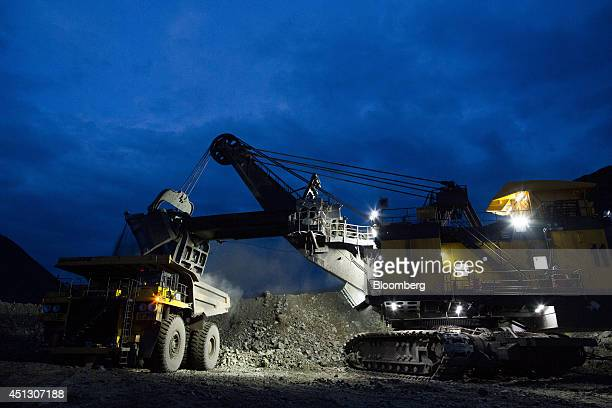 Lights illuminate a shovel loader as it deposits excavated rock into a truck during night mining operations in the open pit at the Neryungrinsky mine...