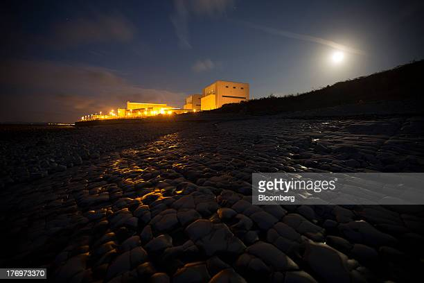 Lights illuminate Electricite de France SA's Hinkley Point A nuclear power station as it stands at night on the bank of the Bristol Channel near...