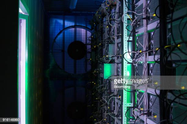 Lights illuminate ethernet cables on mining rigs inside a shipping container converted into a mobile cryptocurrency mining farm operated by...