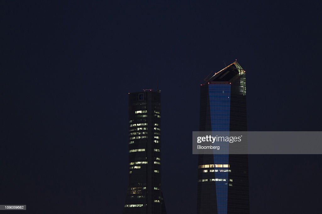 Lights illuminate offices in commercial buildings at night in Madrid, Spain, on Sunday, Jan. 6, 2013. In December, the Spanish parliament passed an energy law that imposed a 7 percent tax on electricity generation from Jan. 1 to plug the deficit. Photographer: Angel Navarrete/Bloomberg via Getty Images