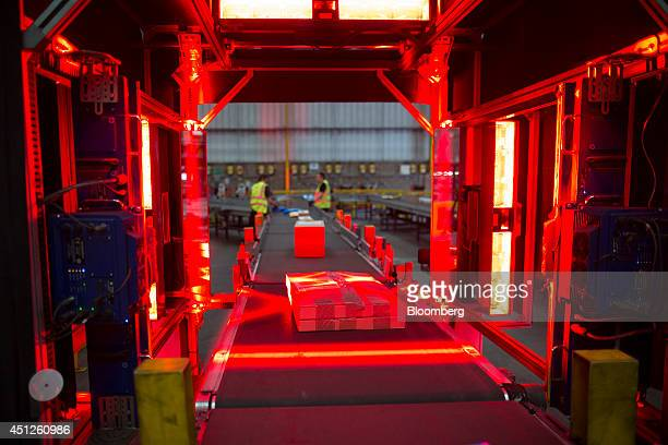 Lights illuminate packages as they pass through a scanning machine ahead of loading for delivery at UK Mail Group Plc's letter and parcel sorting...