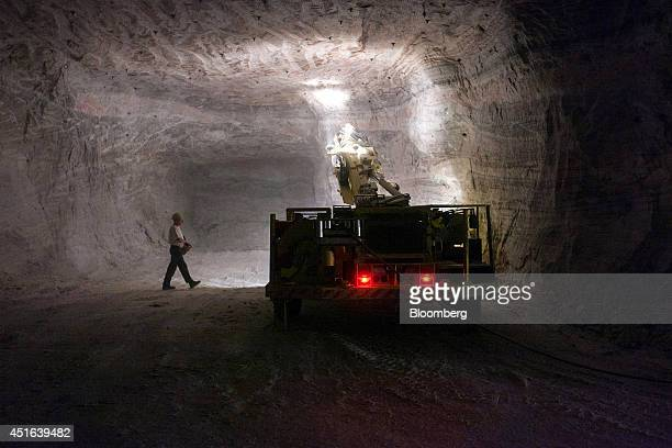Lights illuminate the face of a tunnel as an employee uses a drilling machine during underground operations to extract crude salt used to make potash...