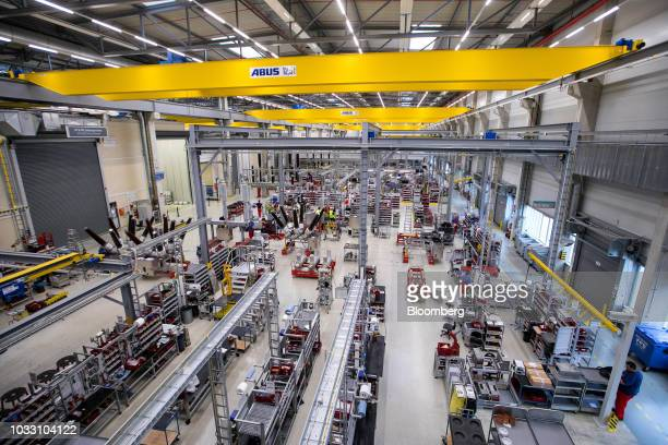 Lights illuminate the high voltage circuit breaker assembly line factory floor inside Siemens AG switchgear electronic power unit factory in Berlin...