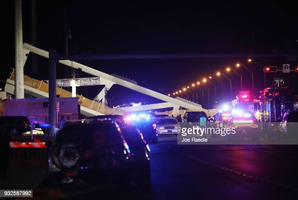 Lights illuminate the scene as MiamiDade Fire Rescue Department personel and other rescue units work at the scene where a pedestrian bridge collapsed...