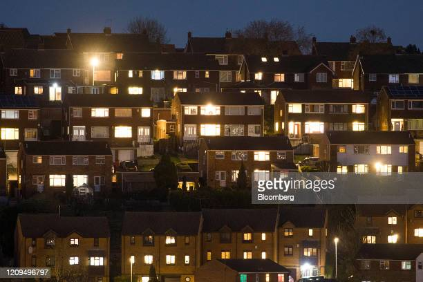 Lights illuminate the windows in residential properties in High Wycombe, U.K., on Monday, April 6, 2020. Among the decisions that my need to be made...
