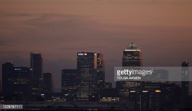 Lights illuminate the windows of the office buildings in the Canary Wharf financial and business district in east London on November 24 during...