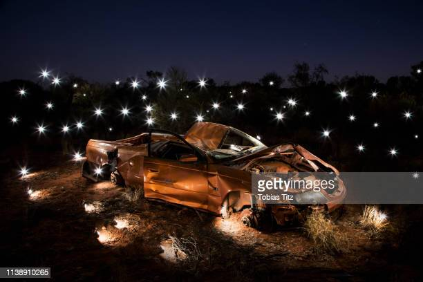 lights illuminating art installation of crushed car - installation art stock pictures, royalty-free photos & images
