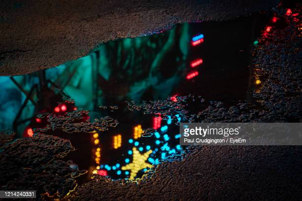 lights of a fairground ride reflected in a puddle of rainwater at night. - night stock pictures, royalty-free photos & images