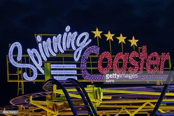 Luces de una atracción llama Spinning funfair en una montaña rusa
